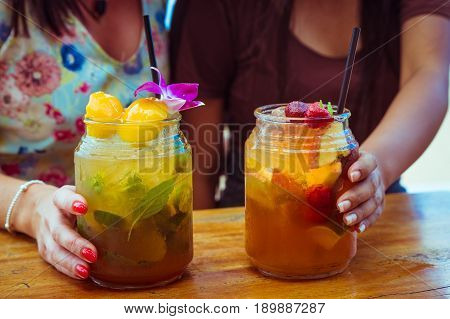Close up of two women in colourful dresses holding glasses with refreshing strawberry apple cocktail with lime and peach mint cold coctail.