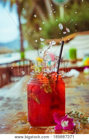 Close up of glass with refreshing strawberry cocktail with lime, mint with splashes on beach bar background.