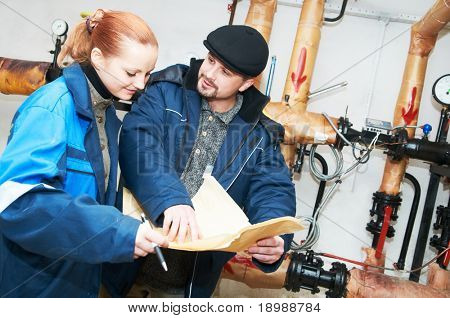 Two engineers discussing technical plan of heating system in a boiler room