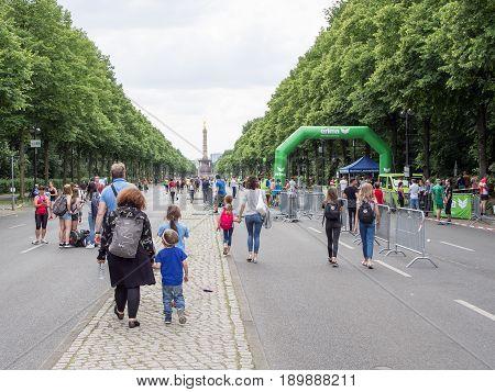 BERLIN GERMANY - JUNE 5 2017: Spectators And Athletes Leaving The International German Gymnastics Festival in Berlin Victory Column In Background