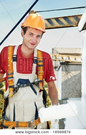 Young smiling painting facade builder worker with roller in work wear