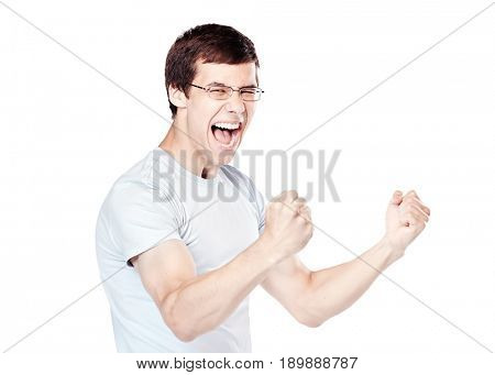 Young hispanic man wearing glasses and blue t-shirt standing and happy screaming celebrating win with raised fists isolated on white background - sports fan support or success concept