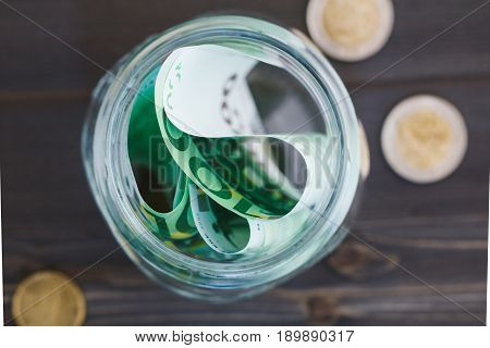 Top view of glass jar for saving Euro money on a wooden dark table.