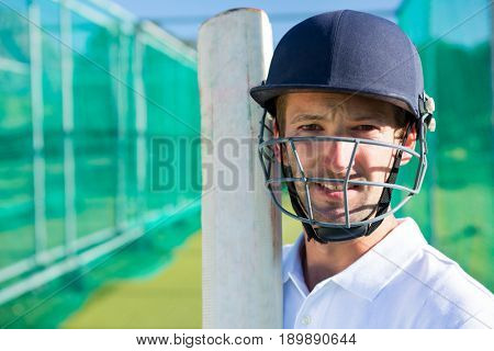 Portrait of confident cricket player wearing helmet holding bat at pitch