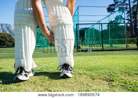 Low section of cricket player tying kneedpad while standing on grassy field