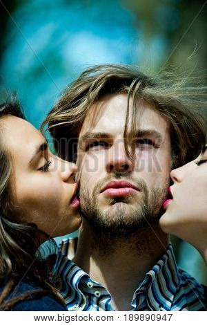 people man or bearded macho with beard getting kiss by two adorable girls or cute women on sunny day on blurred natural blue background. Love triangle. Relationship