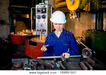 A portrait of a female worker operating a lathe