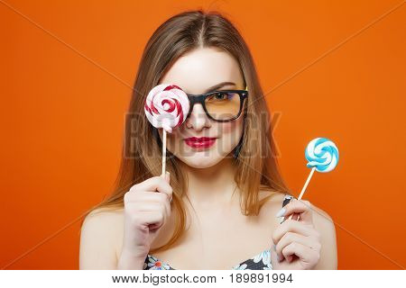 Portrait of Young Girl in Eyeglasses Holding Two Lollipops in Hands on Orange Background. Brunette with Red Lips and Candy in Studio.