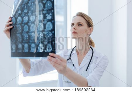 With attention to every detail. Qualified involved professional radiologist working at the clinic while examining x ray and preparing diagnose verdict