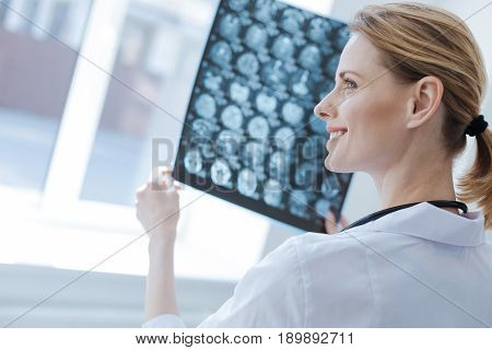 Confident in this diagnose. Delighted smart proficient neurosurgeon working at the x ray laboratory while examining brain x ray and analyzing patient health