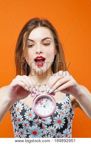 Sensual Brunette Holding Pink Alarm Clock in Hands in Studio on Orange Background. Time Concept.