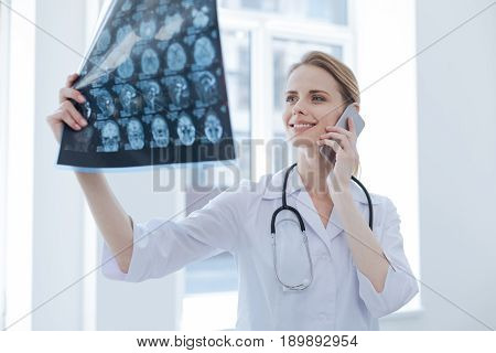 Informing positive news. Upbeat lively young radiologist working at the x ray cabinet while examining brain x ray and using smartphone