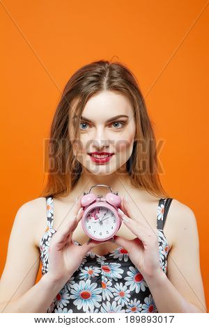 Attractive Brunette with Pink Clock in Hand is Posing on Orange Background in Studio. Time Concept.