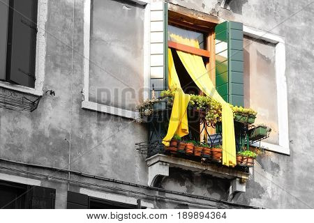 Venice, Italy, May, 31, 2017: facade of an inhabitable house with the open balcony and fluttered curtain in Venice, Italy