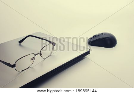 Laptop computer with wireless black mouse and eyeglasses vintage color tone effect selective focus copy space
