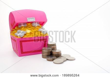 Piggy bank or Treasure Chest shaped money box with coins on white background in saving money concept copy space