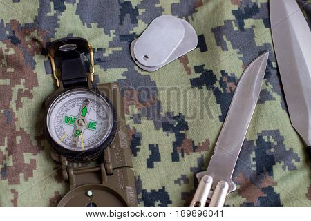 Knives army token and compass against the background of camouflage.