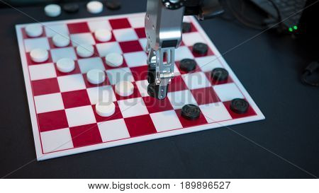 Robot playing checkers hand manipulator moves checkers