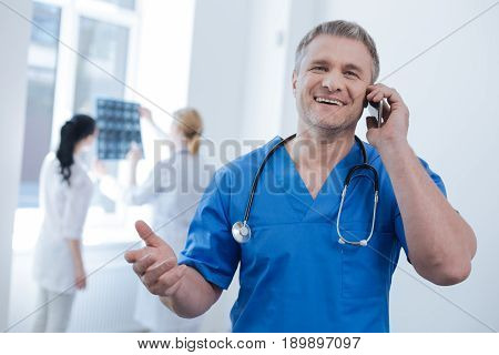 Sharing awesome mood. Charming positive handsome radiologic technologist working at the medical lab and enjoying conversation on the phone while other doctors examining x ray photo in the background