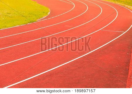 Empty red running track in stadium closeup