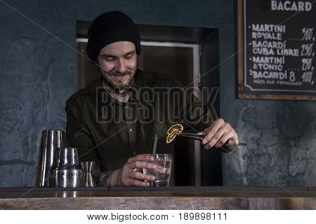 Smiling bartender is making a cocktail in a bar