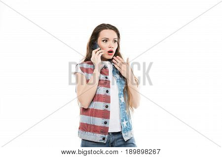 astonished girl in american style vest talking on smartphone with facial expression