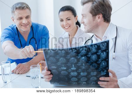Detecting brain problems before operation. Friendly skilled optimistic neurologists working at the clinic and examining brain x ray photo while enjoying conversation and making notes