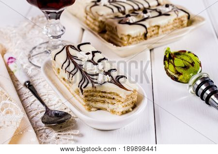 Pieces of biscuit cake with cream layers and chocolate decoration. Selective focus.