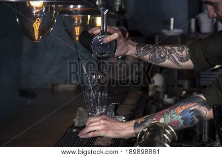close up of stylish barman making a cocktail in a bar