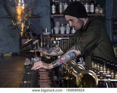 stylish barman serving the cocktail in a bar