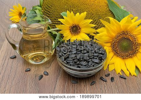 Sunflower oil and seeds on a wooden background. Horizontal photo.