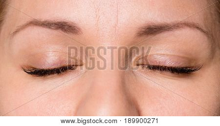 Close-up face of beautiful young woman with beautiful big eyelashes and eyebrows. Macro of human eye - close.