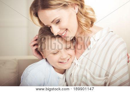 Close-up Portrait Of Happy Mother And Cute Little Son Hugging Together At Home