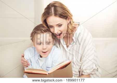 Excited mother and son sitting embracing and reading book together