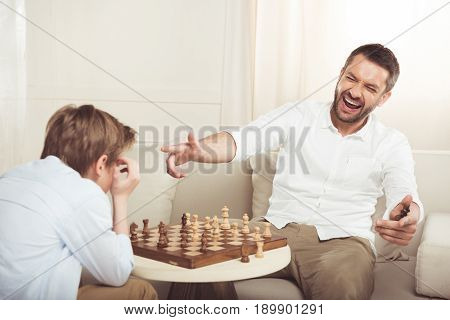 Man Celebrating Win In Chess Game And Pointing At Upset Son Near By