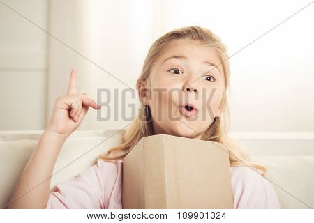 Portrait Of Excited Blonde Girl Holding Book And Having An Idea At Home