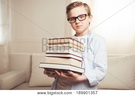 Confident Schoolboy Wearing Eyeglasses And Holding Pile Of Books At Home