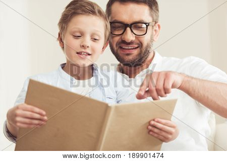 Little Son With Father Reading Book At Home Together