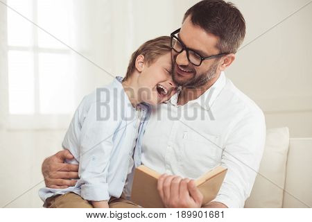 Portrait Of Father And Little Son Reading Book At Home