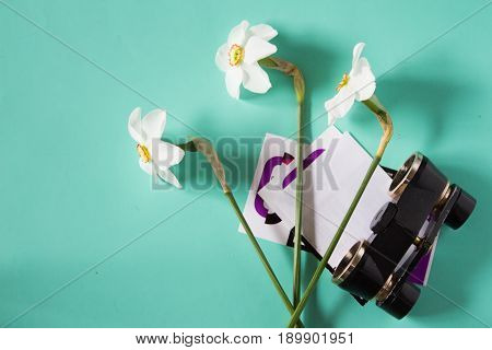 Black Binoculars, Narcissus Flowers And Theater Tickets. Trip To The Theater. Top View. Neutral Back
