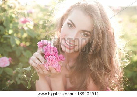 Smiling beautiful blonde woman 24-29 year old holding rose flower posing in meadow outdoors. Looking at camera. Summer time.