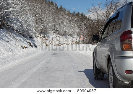 SUV car on snow covered mountain road. winter road in the morning. Car tires on winter road covered with snow