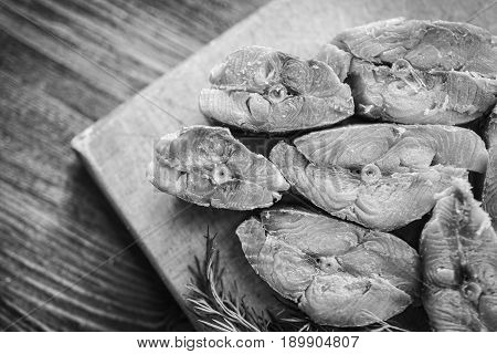 Steaks of red smoked salmon fish and fresh green dill on a light wooden cutting board on a dark wooden background black and white frame