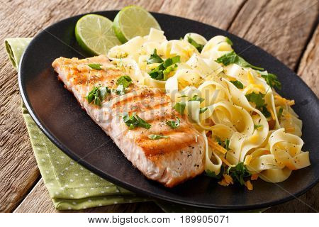 Healthy Food: Grilled Salmon And Fettuccine Pasta With Cheese And Herbs Close-up. Horizontal