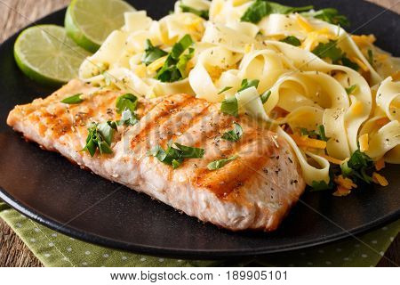 Grilled Salmon Garnished With Fettuccini Pasta With Cheese, Herbs Closeup. Horizontal