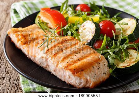 Tasty Fillet Of Grilled Salmon And Vegetable Salad With Arugula Close-up. Horizontal