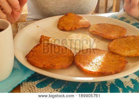 Delicious Potato Pancakes On Plate With Sour Cream