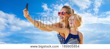 Mother And Daughter With Digital Camera Taking Selfie