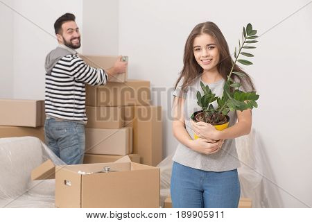 Yung adults moving in new home. Smiling man and woman unpacking boxes after relocation. Man and woman standing in new apartment unpacking boxes.