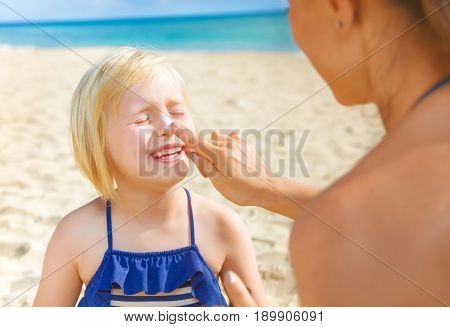 Happy Young Mother And Daughter On Beach Applying Spf